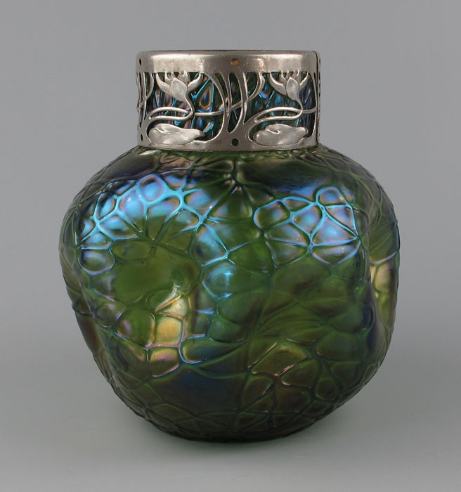 Art Nouveau iridescent glass/ornament vase with a metal frame.