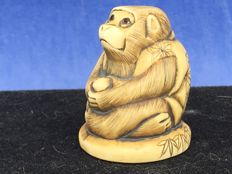 An ivory Netsuke of a monkey with a piece of fruit – Japan – circa 1920