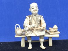 An ivory Okimono of a man on a bench eating lunch – Japan – late 19th century
