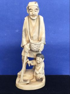 A solid ivory Okimono of a field worker with child - Japan - approx. 1920
