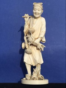 An ivory Okimono of a farm labourer with a rake, signed – Japan – late 19th century (Meiji period)