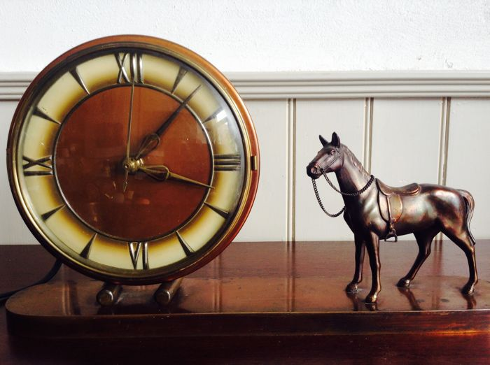 Standing copper dresser clock with a figurine of a horse