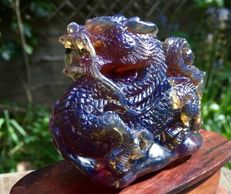 """Blue & """"Dragon blood"""" play of colours - untreated Amber Dragon figure on mahogany stand, one piece carving on stand, over 72 grams"""