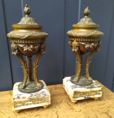 A pair of zamak chimney pieces, lidded coupes on marble base - France - ca. 1900