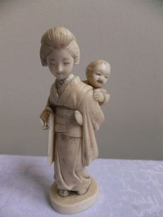 Signed ivory okimono of a lady carrying a baby on her back - Japan - ca. 1930s (Taisho period/early Showa period)