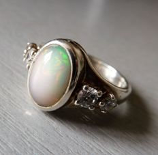 Ring in solid silver set with two white gems and a natural harlequin opal cabochon.