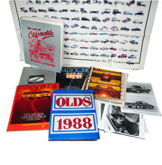 """The cars of Oldsmobile"" (the Oldsmobile bible) plus 3 big, brand new 1987 brochures, a 100 years anniversal press kit (1997), a 1988 press kit and a 50x90 cm anniversary poster with 100 cars."