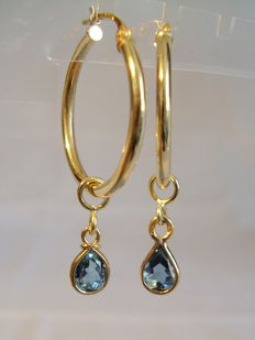 14 kt gold creole earrings with faceted blue topaz drops totalling 1 ct.