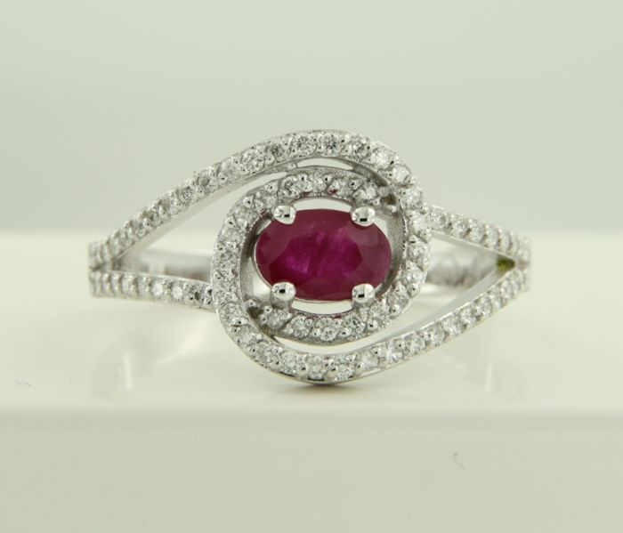 14 kt White gold wavy ring set with a central oval cut ruby and 70 brilliant cut diamonds, ring size 17.5 (55) ***NO RESERVE PRICE***