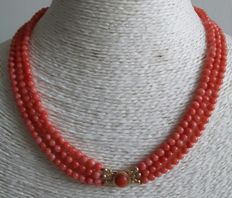Necklace of three strans of red coral with a gold clasp.