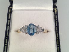 Yellow gold ring with a blue topaz and brilliant cut diamonds, 0.36 ct, ring size 17.25/54