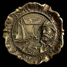 A vintage  golden bronze circular plaque with a fisherman smoking a pipe , near a coastal landscape