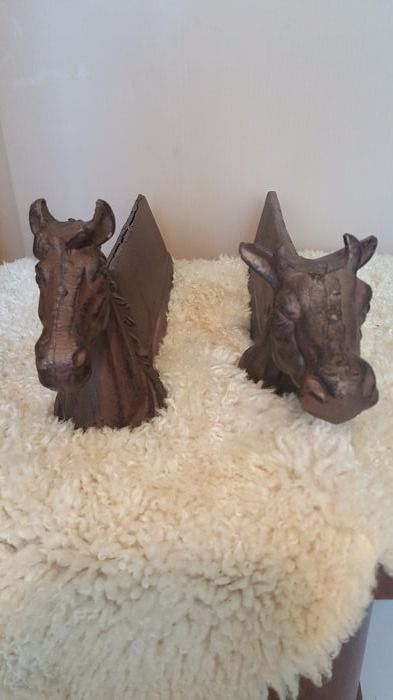 Set of two cast iron andirons with a horse- and a cow head