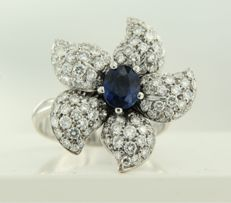 18 kt white gold ring shaped like a flower, set with a central sapphire and 102 brilliant cut diamonds of approx. 2.50 ct in total