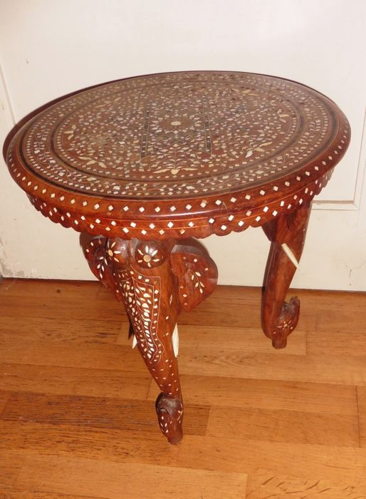 Carved wood coffee table with elephant shaped feet.