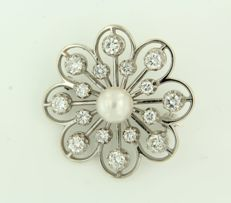 14 kt white gold brooch set with a central cultured pearl and 16 brilliant cut diamonds, approx. 1.50 carat in total.