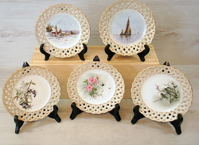 Five antique German porcelain hand painted cakes plates on wooden stand