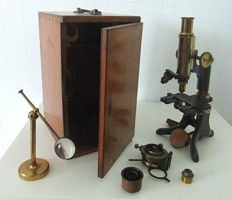 A 19th century lacquered brass monocular microscope by Baker, 244 High Holborn, London, in fitted mahogany box with a further collection of related lenses and accessories and telescopic pieces.