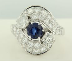 Platinum ring set with a central 1.40 ct brilliant cut sapphire and two brilliant cut diamonds, 1.00 ct, surrounded by an entourage of 32 brilliant cut diamonds, 1.80 ct, ring size 17.5 (55)