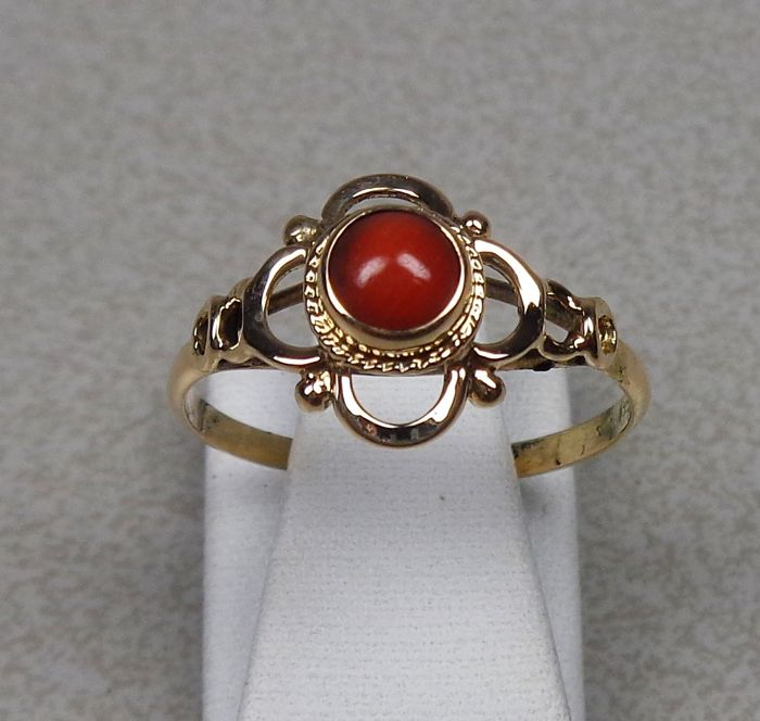 A 14 karat ring with red coral.