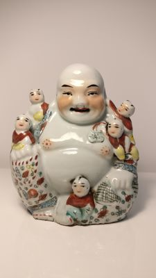 Cheerful porcelain Buddha with children seated on him – China – mid 20th century