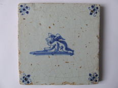 Antique tile with a crawling Cupido.