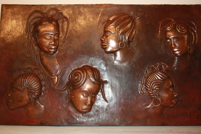 Large copper wall plate depicting six different hairstyles in Africa