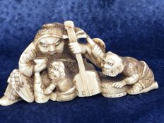 An ivory Okimono of a Samurai with Samisan, surrounded by Devils - Japan - around 1900-1930