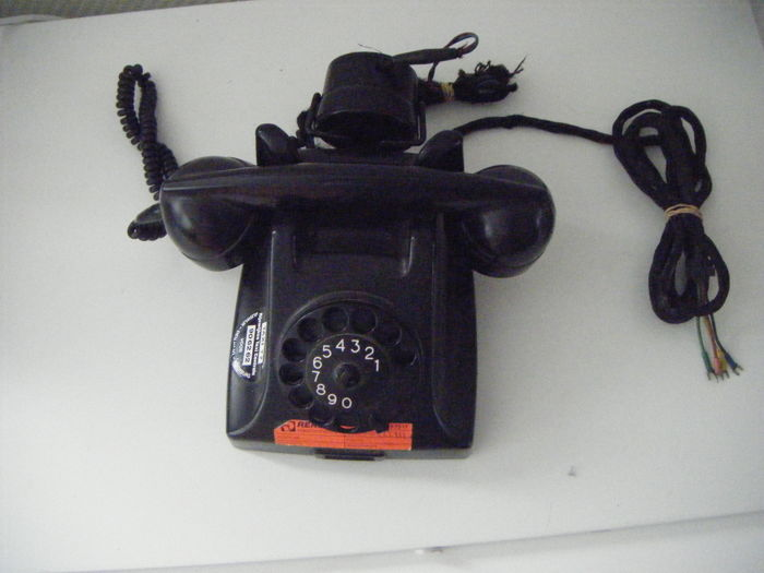 Antique Bakelite PTT telephone with a dial and an earpiece for listening in