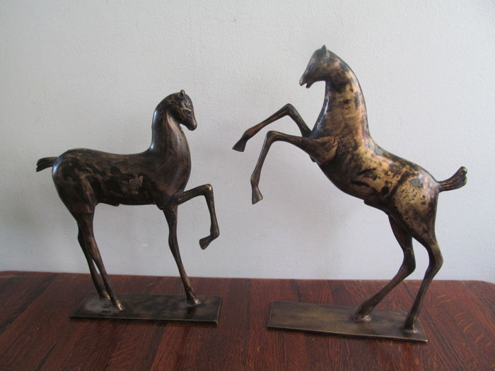 Two burnished metal horse sculptures.