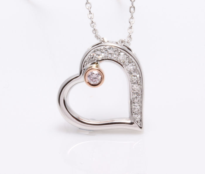 Pendant in the shape of a heart with a natural pink diamond, decorated with 9 diamonds, 0.20 ct in total.