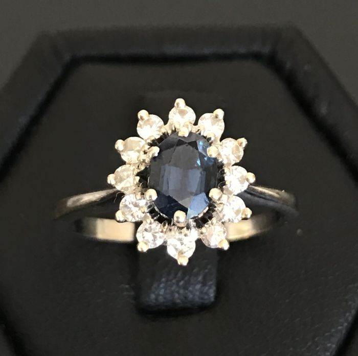 18 kt grey gold daisy ring with a royal blue sapphire in centre (1.10 ct) in a crown of diamonds H/VS (0.36 ct) – ring size: 54 – 6 3/4.