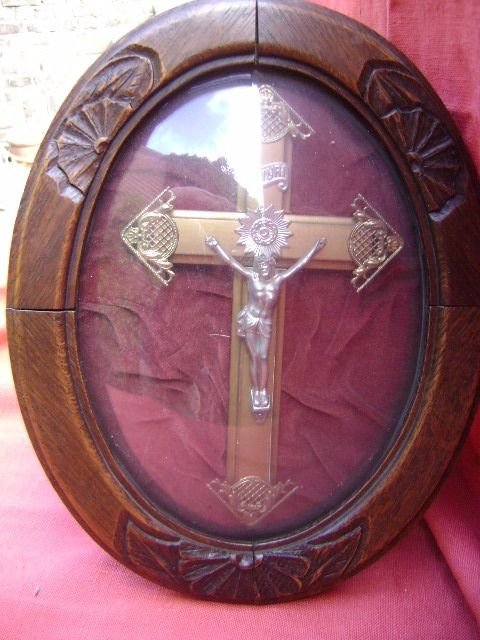 Gilded crucifix behind convex glass in wooden frame.