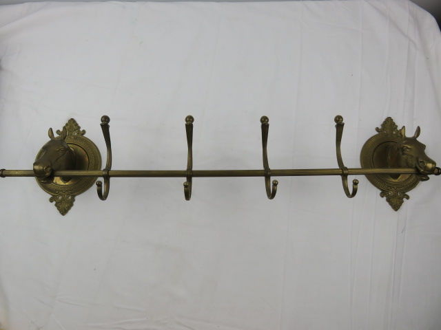 Coat hanger made of brass with 2 horse heads.