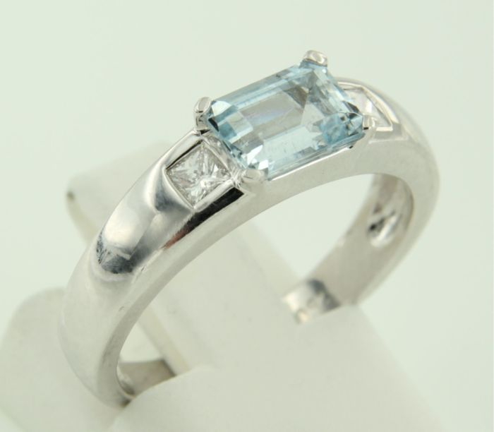 18k white gold ring set with blue topaz and 2 princess cut diamonds, approx. 0.20 carat in total, Ring size 16.5 (52)
