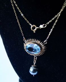 Handcrafted elegant necklace in yellow gold with a faceted large blue natural Topas ca. 5 ct VVS1 and  real natural gray Tahitian pearl ca. 8,9mm. Wonderful state.