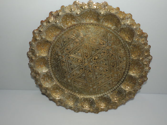 Platter with scalloped rim in solid bronze - decorated with geometric patterns, flowers and ears - diameter: 44 cm –  Maghreb – ca. 1950.