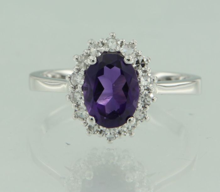 14 kt white gold entourage ring with a central 1.15 ct oval cut amethyst and an entourage of 14 single cut diamonds, ring size 16.5 (52)