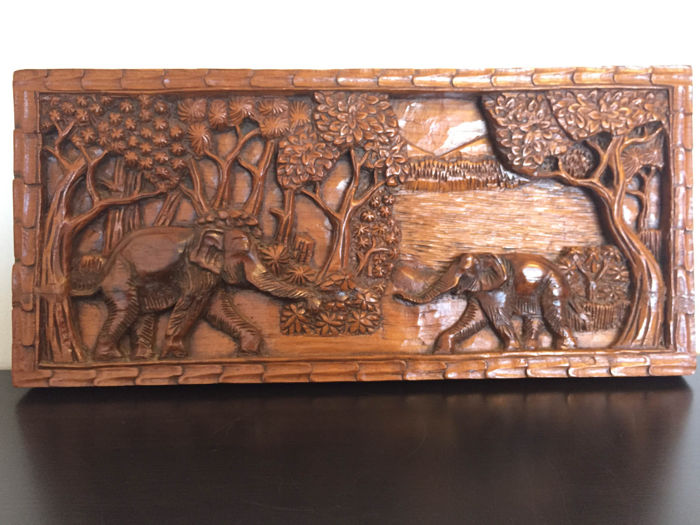 Wood carving in depth relief depicting elephants