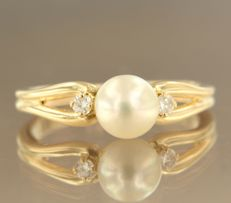18 kt yellow gold ring set with a central pearl and two brilliant cut diamonds, approximately 0.09 carat in total, ring size 17.5 (55)