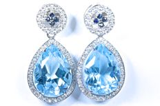 18 kt.  White gold earrings set with 80 GH-SI diamonds, two large blue natural topazes in droplet shape and eight blue sapphires, colour A. Length: 26.60 mm. No reserve price.