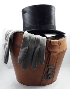 Classic top hat with 2 grey fabric gloves in large brown leather hatbox, Mid 20th century
