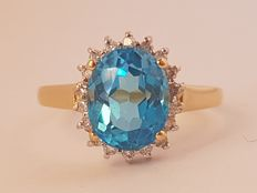 Gold 14 kt rosette ring set with a blue topaz of 6 ct and 18 brilliant cut diamonds of approx. 0.36 ct in total