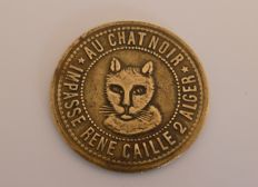 "Algeria (French colony) – Token from the brothel ""Au Chat Noir / Maison Jeanne"", Algiers, around 1930."