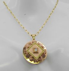 Yellow gold chain with yellow and rose gold pendant with a central diamond