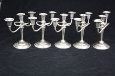 Five ornate silver-coloured English candlesticks