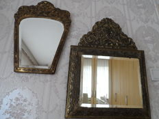 Two copper alloy mirrors, studded, with wooden cabinet