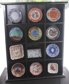 "Porcelain collection of ""Die Schätze der Kaiserhöfe"" - Japanese miniature plates on collection shelves"