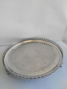 Large round silver plated tray with supporting legs and perforated railing.