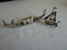 Silver Oriental boat with 2 people and Dutch silver sailing boat.